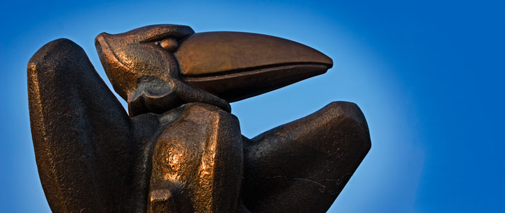 bronze jayhawk statue against a blue sky