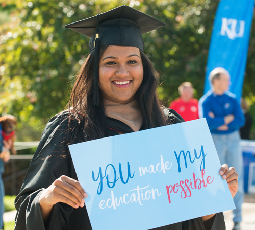 graduating female with thank you sign